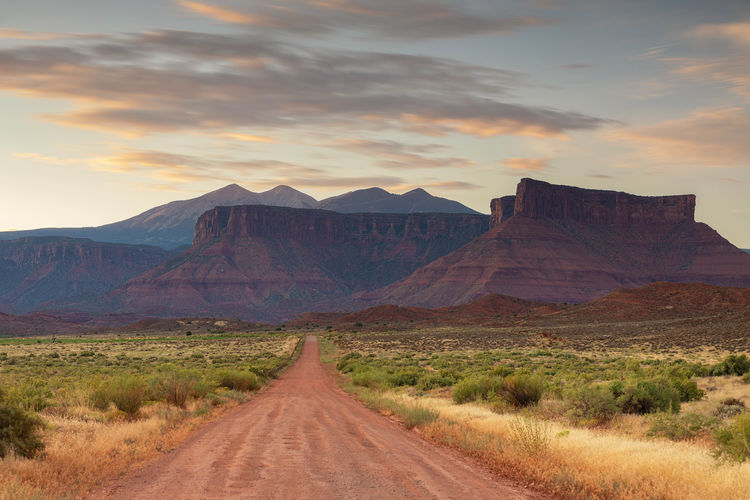 Dirt road leading towards mountains against sky