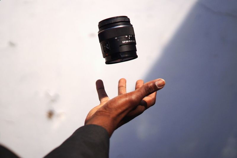 Close-up of hand throwing camera lens