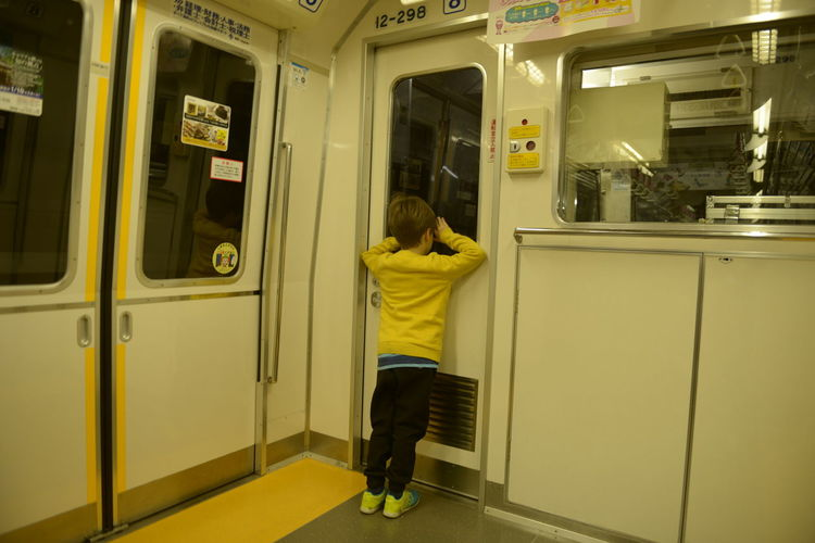 Full length rear view of boy peeking through door while boarding metro train