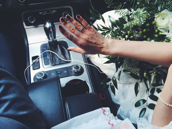 Midsection Of Woman Showing Wedding Ring In Car