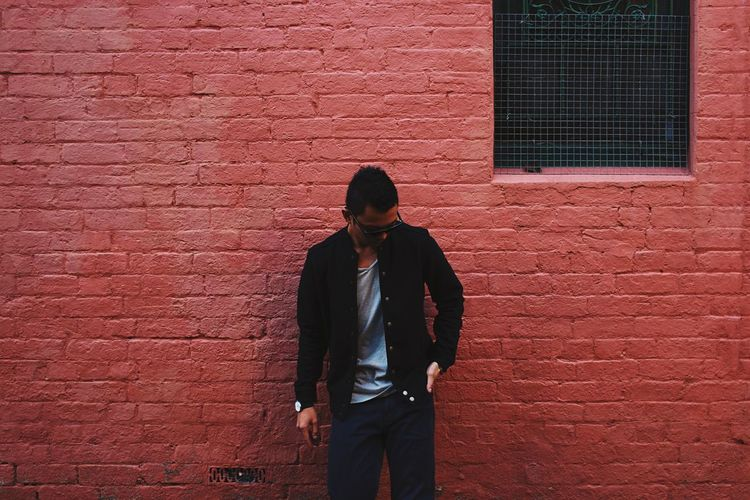 Man standing on brick wall