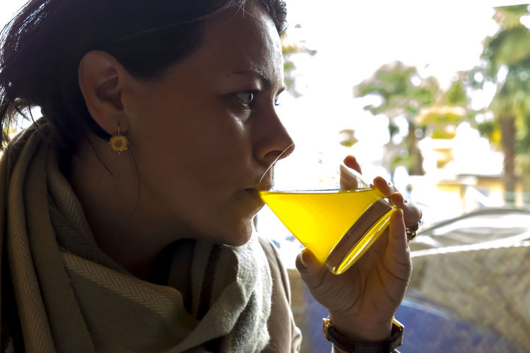 Woman drinking Orange juice. Drinks Profile Close-up Contemplation Day Drink Drinking Drinking Glass Focus On Foreground Glass Headshot Healthy Lifestyle Holding Leisure Activity Lifestyles Looking Looking Away One Person Orange Juice  Portrait Real People Refreshment Women