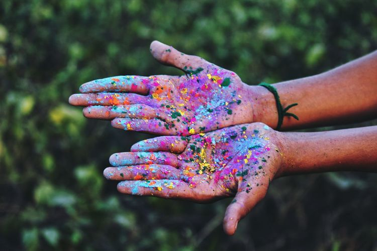 Close-up of hands covered in colorful paint
