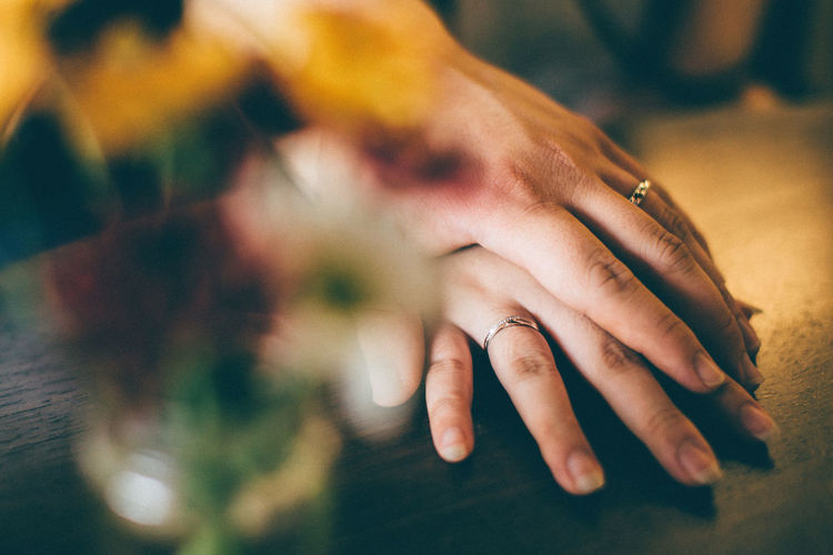 Cropped hand of man holding woman hand on table