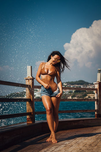 Smiling Beautiful Woman Removing Hot Pants While Walking On Pier Against Sea