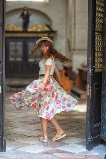Full length of young woman dancing on floor seen through open door