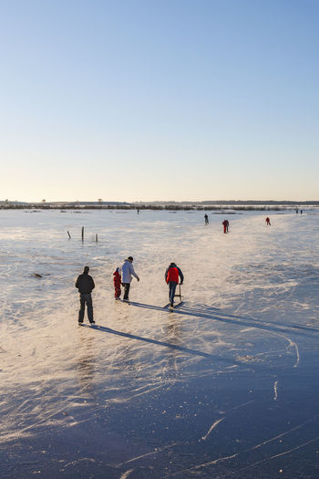 People on beach against clear sky during winter