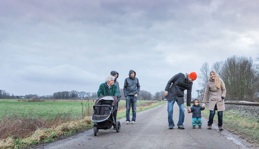 Family walking on road against cloudy sky during winter