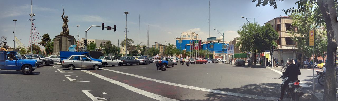 Panoramic shot of cars on city street against sky