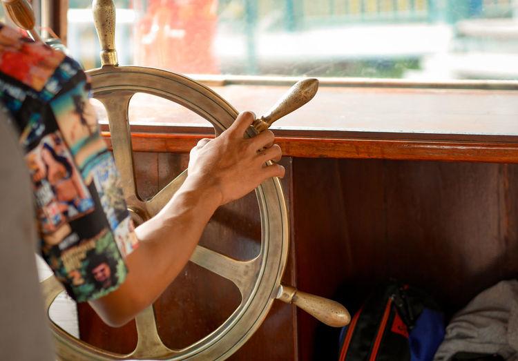 Cropped image of man steering ship