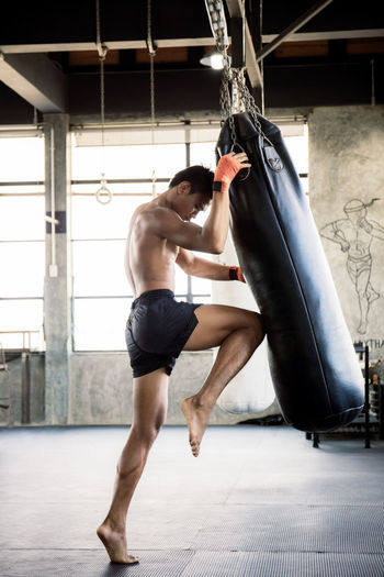 Boxers are training their knees with punching bag at the boxing stadium. Action Adult ASIA Asian  Athlete Attack Attractive Bag Body Bottom Box Boxer Boxing Culture Exercis Fight Fighter Fighting Fitness Gym Hand Healthy Kick Kickboxing Legend Lifestyle Male Man Martial Model Muay MuayThai Muscular person Portrait Proud Punch Punching Bag Ready Sport Strength Strong Thai Thailand Traditional Training Workout Wrapping Young