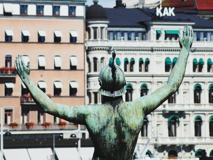 Rear view of statue against buildings on sunny day