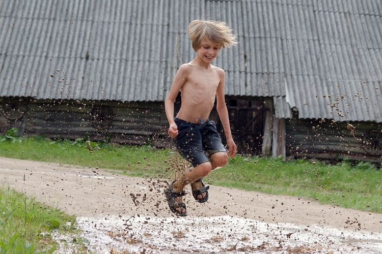 Full length of shirtless boy jumping over muddy puddle