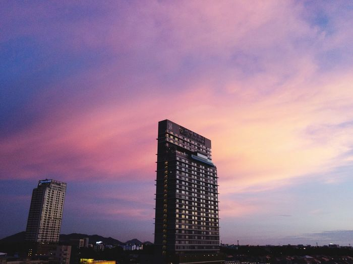 Low angle view of modern buildings against sky during sunset
