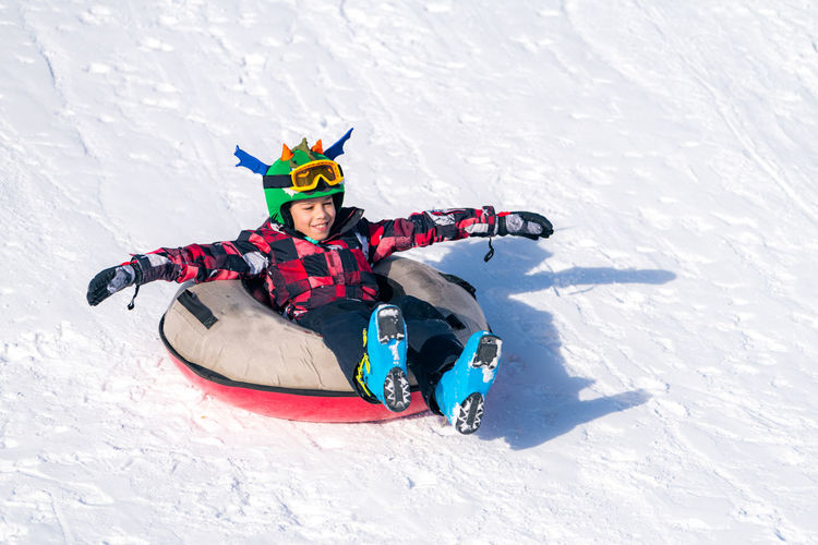Full length of boy over inflatable raft on snow