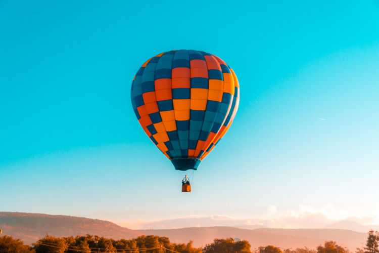 Low angle view of hot air balloon flying in mid-air against clear blue sky