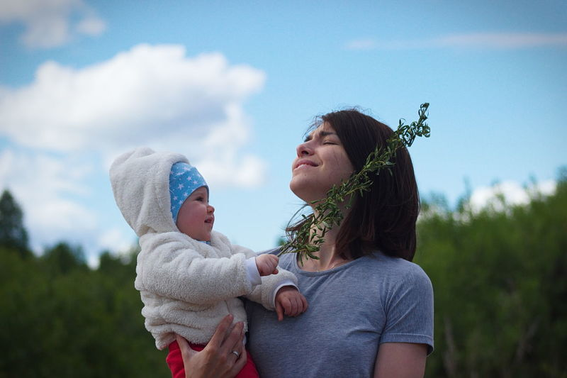 Low angle view of smiling mother carrying cute daughter while standing against sky