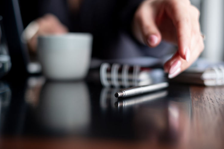 Business woman reaches for a pen lying on the desktop Business One Person Pen Business Finance And Industry Business Person Communication Human Body Part Human Hand Close-up Indoors  Midsection Table Selective Focus Household Equipment Technology Computer Office Finance Copy Space