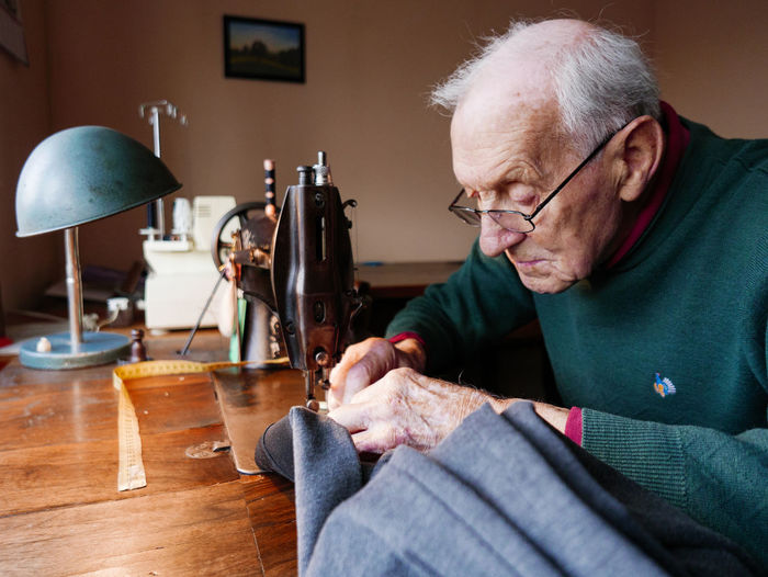 Senior man sewing textile at home