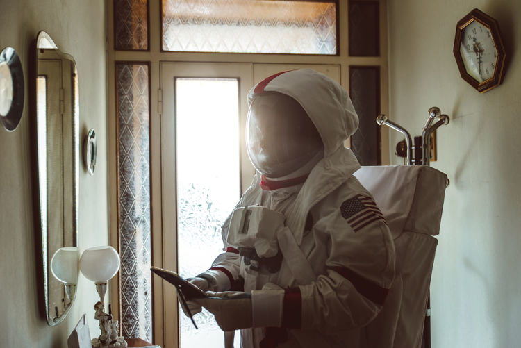 Man using phone while wearing spacesuit at home