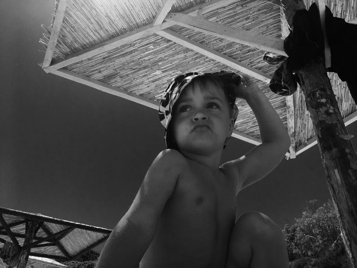 Low angle view of shirtless boy against sky