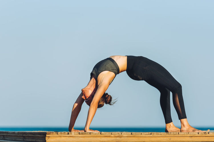 Side view of woman practicing wheel pose on boardwalk against sea