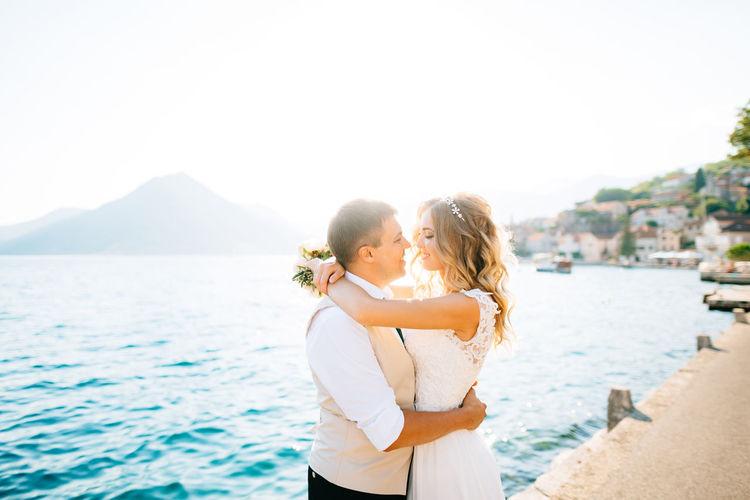 Couple standing near sea against sky