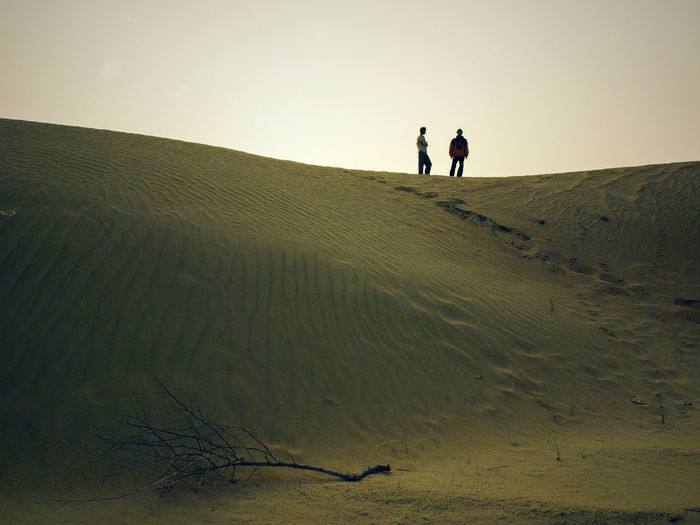 Two People Land Men Leisure Activity Nature Togetherness Full Length Sky Sand Real People Scenics - Nature Beauty In Nature Walking Tranquility Lifestyles Silhouette Standing Tranquil Scene People Sand Dune Arid Climate Outdoors Climate Couple - Relationship Desert Rajasthan Jaisalmer