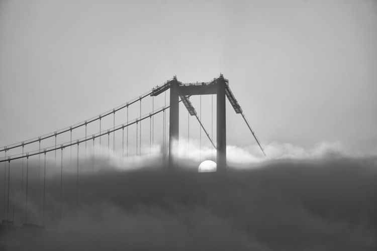 Low angle view of suspension bridge against sky and fog