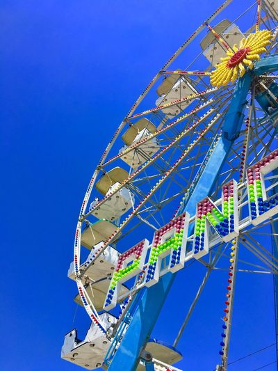 Low Angle View Amusement Park Sky Amusement Park Ride Blue Clear Sky Arts Culture And Entertainment No People Multi Colored Outdoors Ferris Wheel Day Architecture Carnival Chain Swing Ride Sunlight Decoration Nature Built Structure Metal