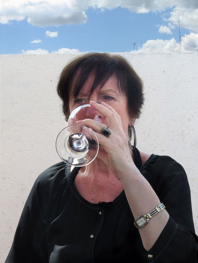 Woman drinking wine while sitting against wall