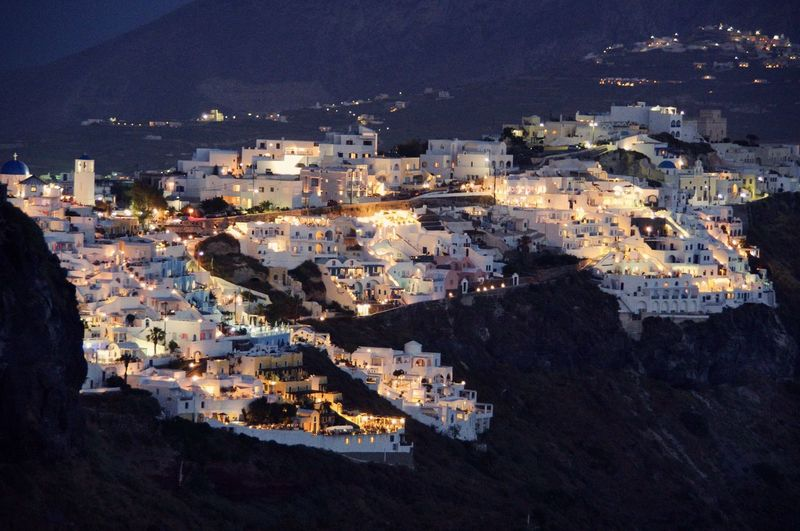 High angle view of illuminated city by sea at night