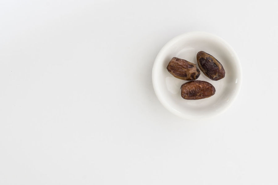 Dates or kurma in white plate over white background Close-up Dates Fasting Food Freshness Kurma Muslim No People Ramadhan Top View