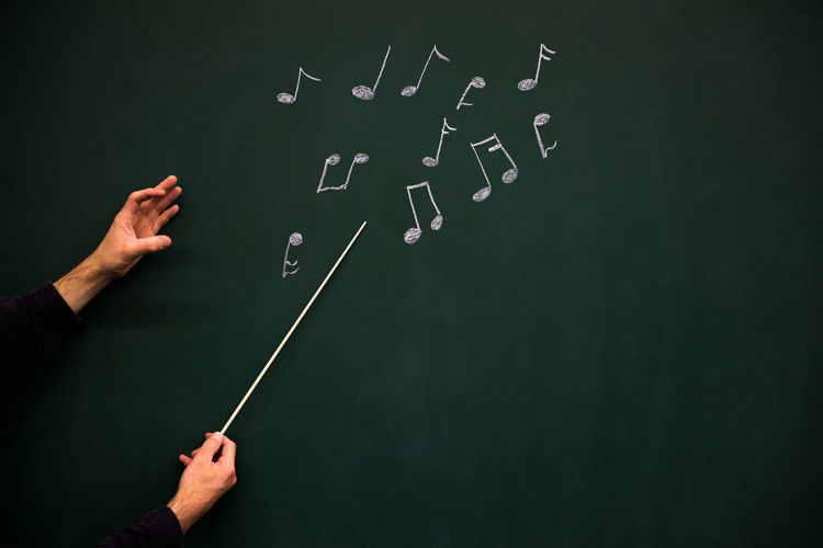 Cropped Hands Of Man Playing With Musical Notes Drawn On Blackboard