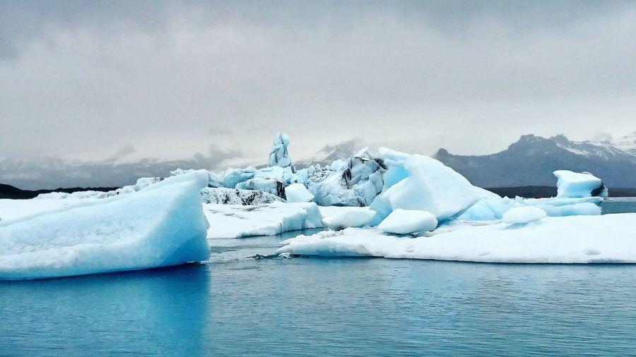 Iceberg In Calm Sea Against The Sky