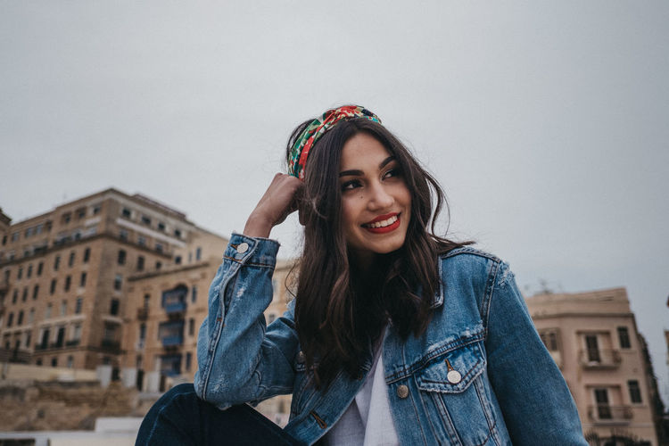 Portrait of smiling young woman against sky
