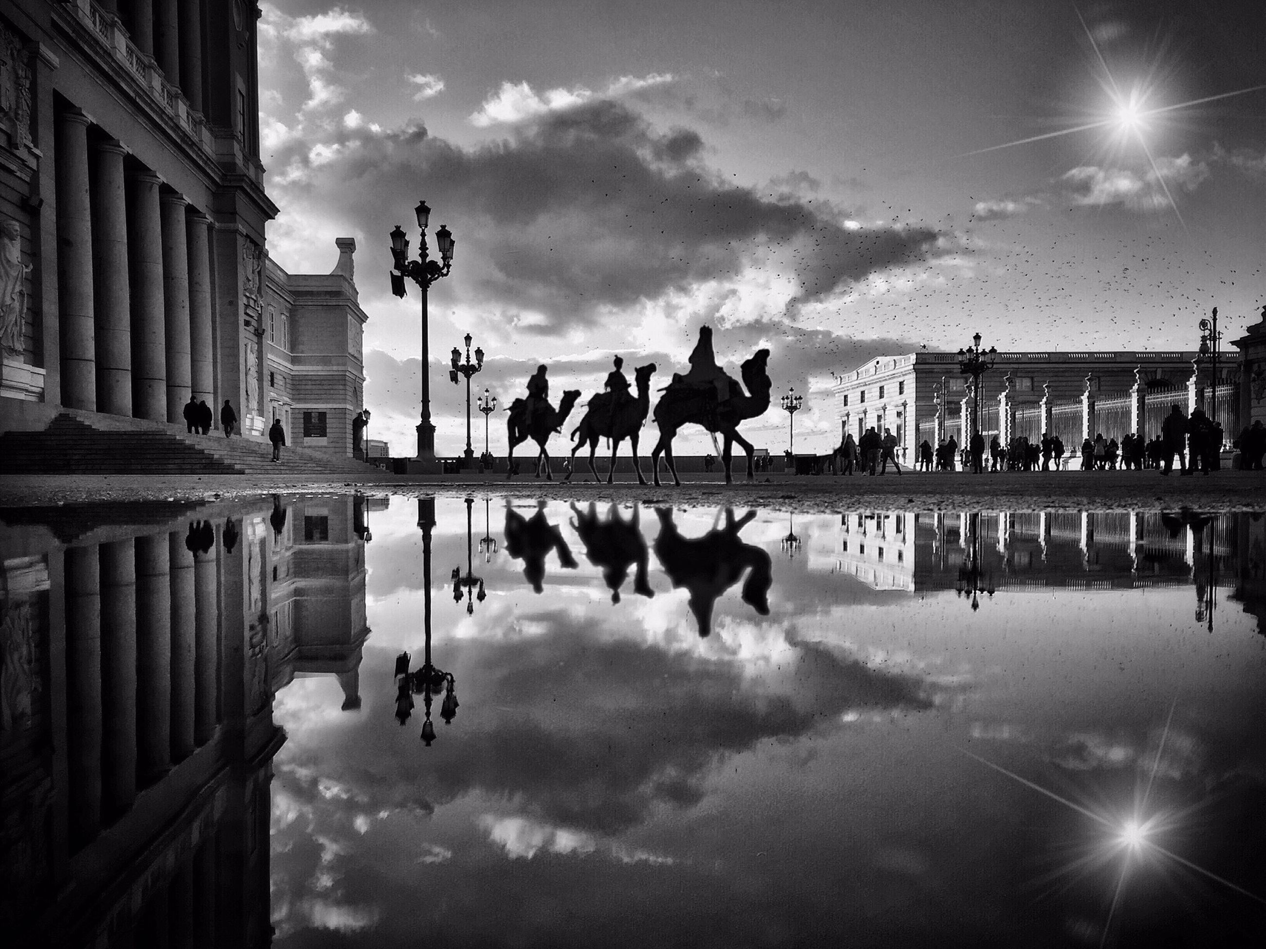 sky, architecture, built structure, cloud - sky, building exterior, silhouette, large group of people, men, lifestyles, cloud, reflection, person, leisure activity, water, cloudy, dusk, medium group of people, walking, mixed age range