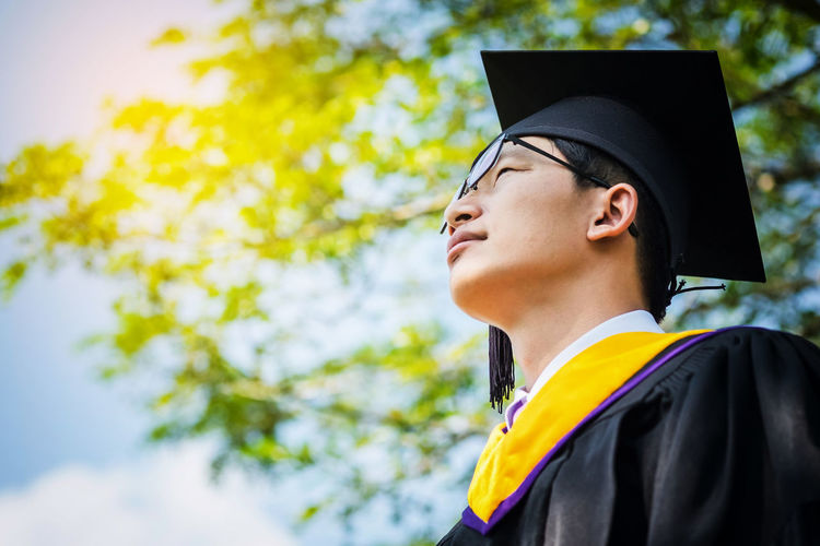 Low angle view of young man in graduation gown standing against sky