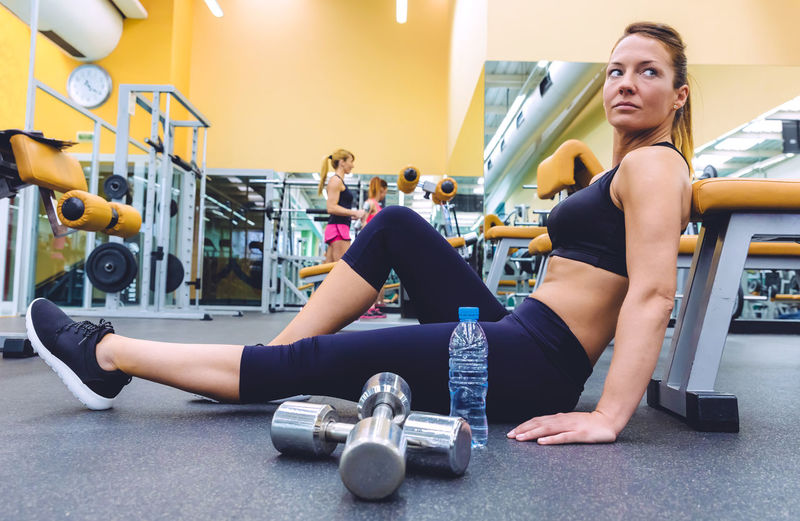 Beautiful sporty woman resting sitting on the floor of fitness center and people doing exercises with dumbbells in the background Athletic Blonde Horizontal Sitting Woman Activity Club Dumbbell Equipment Female Fit Fitness Gym Healthy Lifestyle Indoors  Muscles Muscular Real People Resting Sport Train Training Water Weight Workout