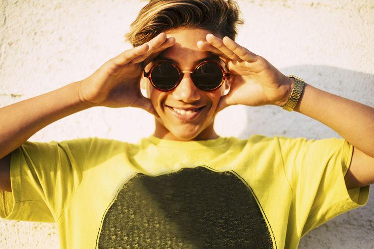 Portrait of smiling teenage boy wearing sunglasses against wall