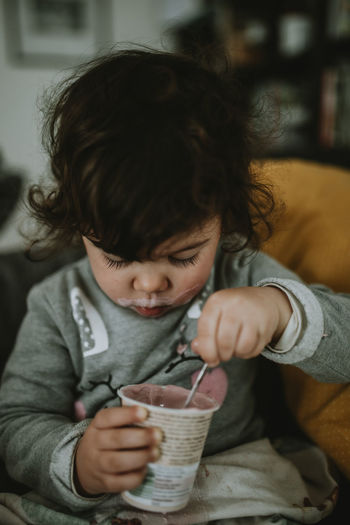 Midsection of a child eating yogurt