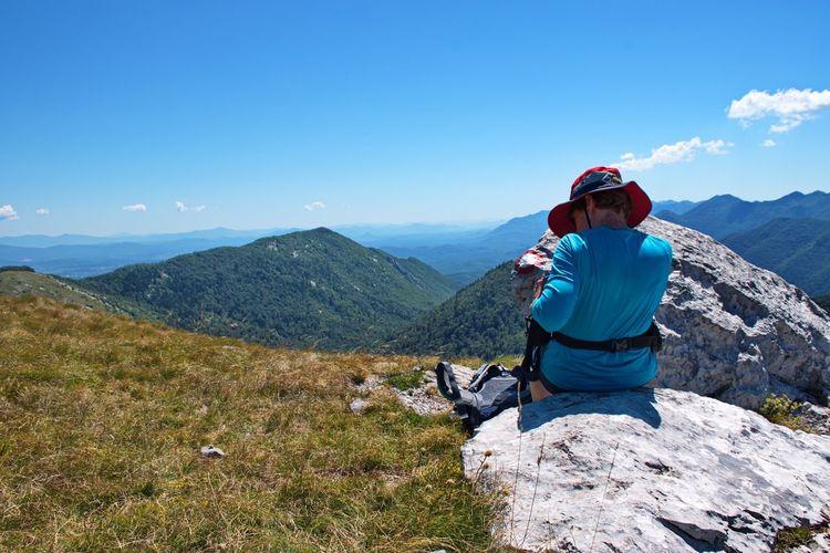 Senior woman sitting on mountain peak with beautiful view in background - velebit mountain, croatia