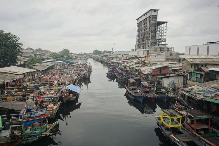 Boats moored in canal amidst buildings in city against sky