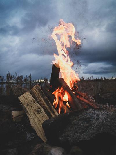 Bonfire by the sea against sky