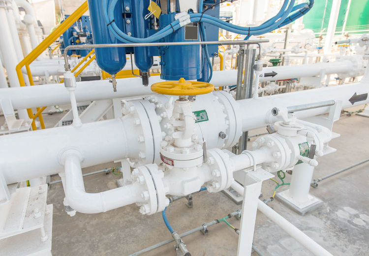 Close-Up Of Yellow Valve On White Pipe At Factory