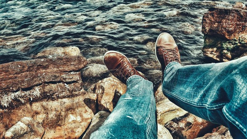 Legs From My Point Of View Seaside Sea Rocks Legsselfie Shoes Human Representation Enjoying Life Taking Photos By The Sea Sunny Day Human Settlement The Human Condition Getting Creative EyeEm Best Edits My Shoes Legs_only Human Body Part Human Leg Shoeselfie Shoes Of The Day Blue Jeans Malephotographerofthemonth