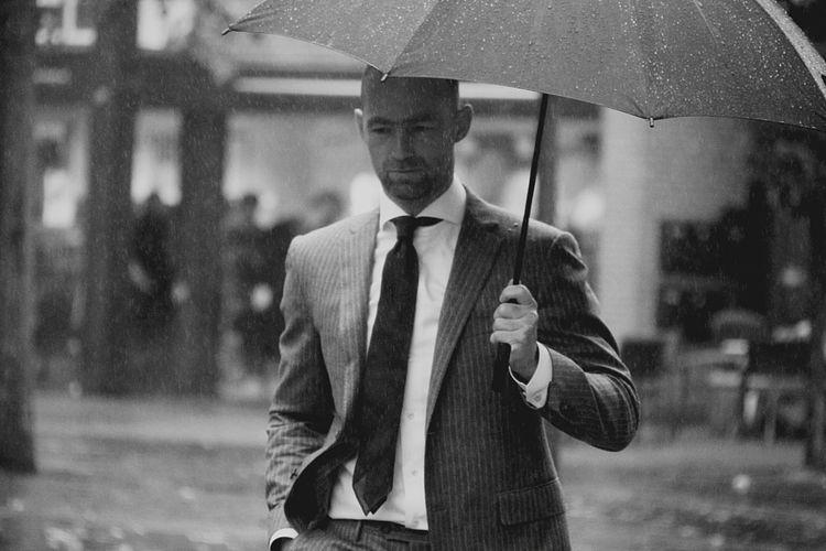 Man With Umbrella Walking On Road In Rain