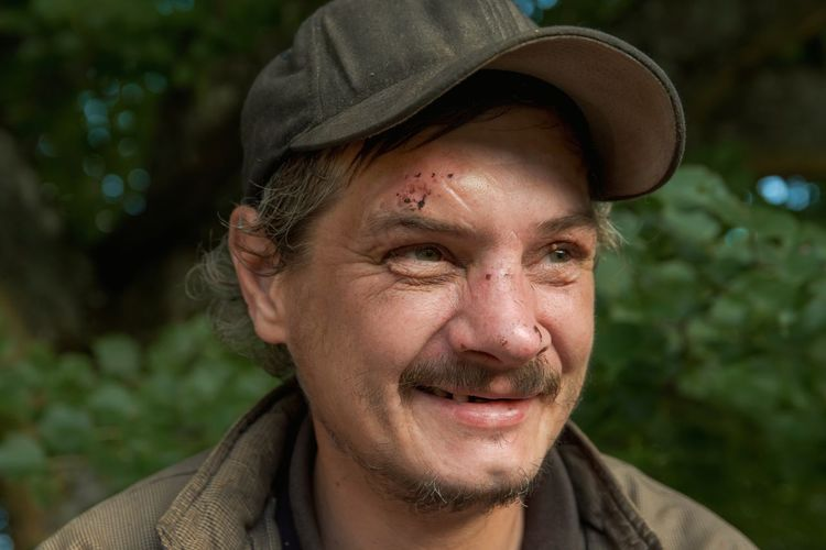 Portrait of smiling man, scratched face, wearing hat