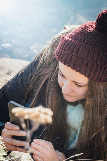 Young woman in warm clothes using mobile phone outdoors