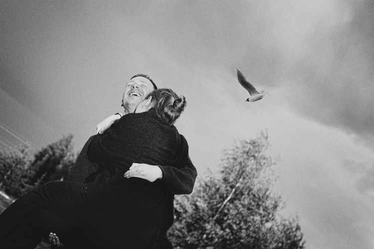 Man lifting girlfriend against sky
